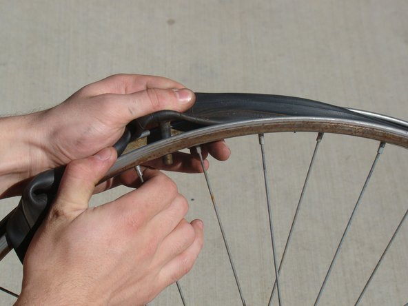 Remove the cap from the inner tube, and pull the valve stem out of the rim.