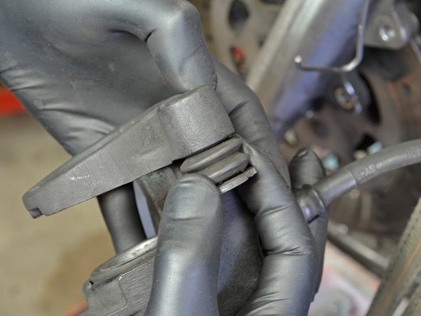 Using your fingers, pull the alignment peg out of its hole in the stationary caliper.