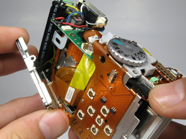 Do not pull the back panel too far, it is connected to the top of the camera with ribbon cables and is not meant to separate from the camera.