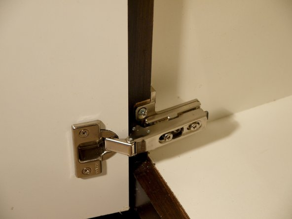 Lift or lower the cabinet door to align the hinges with its original location.