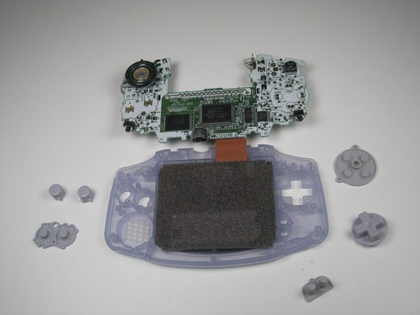 Remove the plastic buttons and the D-pad from beneath the rubber pads with tweezers or by hand.