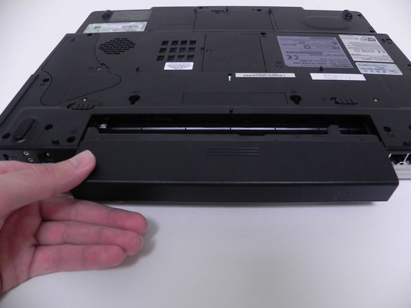 Image 3/3: Remove the battery by sliding it out away from the computer (horizontal with the casing).