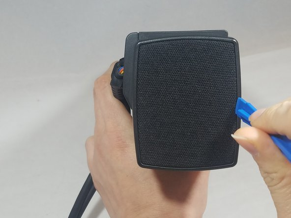 Using the blue plastic opening tool, pry up on the cloth covered end panel. The edge of end cap cover should separate from main body of device.