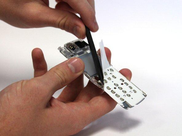 Utilisez le spudger pour éplucher le coin supérieur gauche du film adhésif blanc. Cela peut se faire en faisant fonctionner le spudger en va-et-vient sous le film.