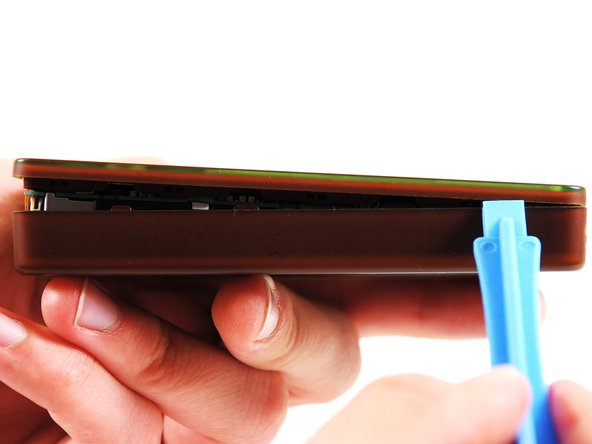 Use the blue plastic opening tool to slowly work your way around the edges of the case, releasing the front plate from the bottom case.