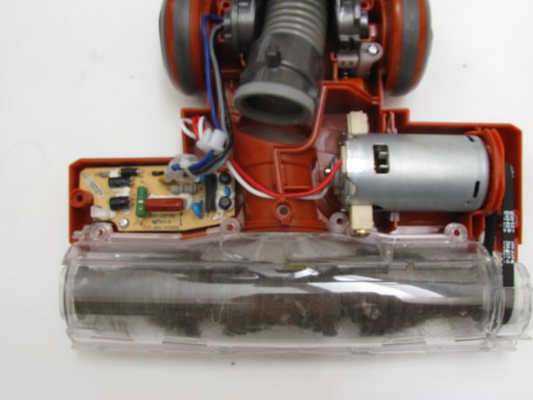 Use a Phillips #2 screwdriver to remove the four visible screws securing the rotary brush to the vacuum.