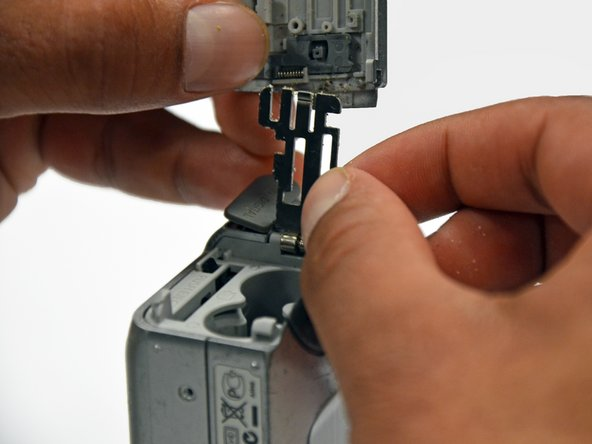 Remove the plastic portion of the battery flap cover. The metal piece will remain attached.