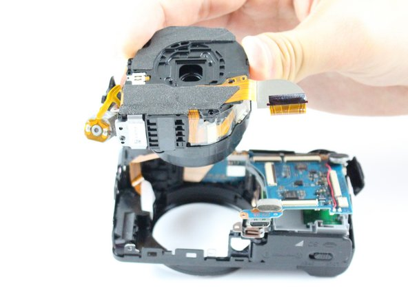 While holding the mainboard in the perpendicular position, use your other hand to carefully lift the camera lens straight up and out of the case.