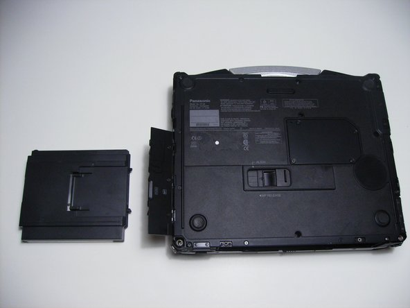 Push the exposed switch to the left to eject the optical drive.