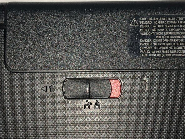 Slide the manual battery latch to the unlock position, so that the red is showing.