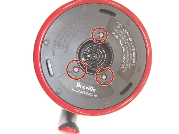 Begin teardown by flipping the kettle upside down. You will see 3  small triangle head security screws (shown in red circles) holding a plastic casing for the base.