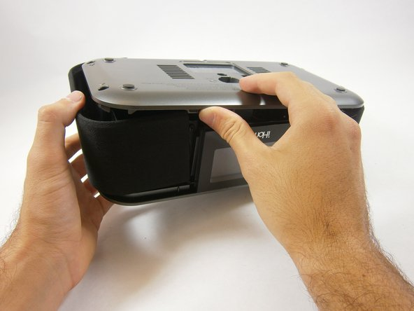 Image 1/2: Lift up the bottom cover. Pull the side panel up first, out, and away from the device.