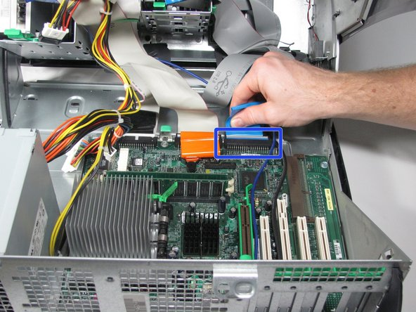 Image 2/3: Disconnect the optical drive ribbon cable by gently pulling the orange tab away from the motherboard.