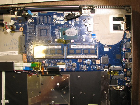 Image 2/2: Remove the motherboard by lifting it up very carefully as the power button ribbon cable is still connected to the left under side of the motherboard. See step 21.