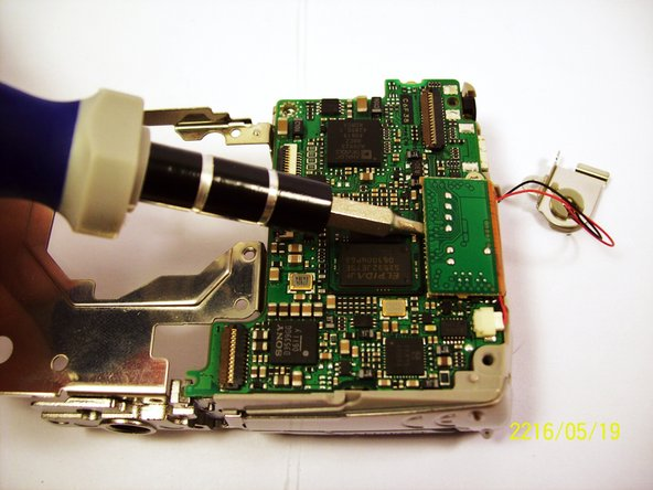 Place a flathead screwdriver and gently lift the circuit attached, as shown on the picture.