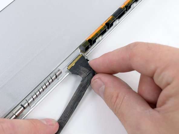 Carefully pull the display cable through its slot in the aluminum housing, rotating it as necessary to fit through the opening.