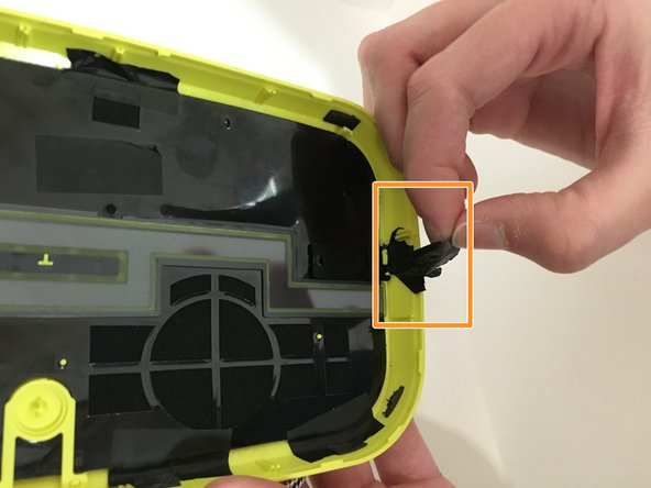 A piece of black tape on the side panel may also be covering the yellow connector tip that holds the volume button in place. Remove the black tape if necessary.