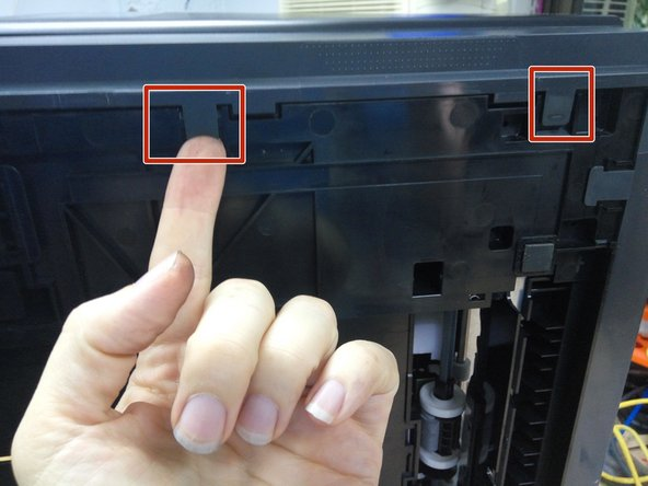 Release the two clips on the underside of the printer.