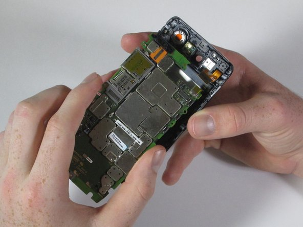 Image 3/3: Use your fingers to gently pull the motherboard down and out of the rear casing.