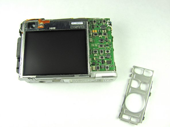 Remove the metal grating located to the right of the LCD screen by inserting the plastic opening tool under the grating and pulling up.