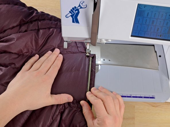 Align the jacket and zipper in the sewing machine.