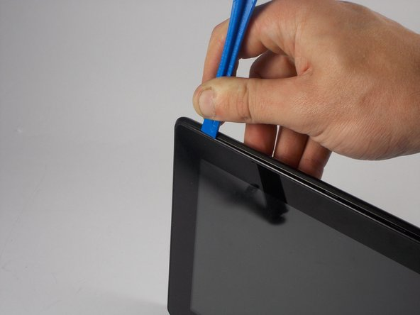 Take the plastic opening tool and insert it into the crease between the screen and the plastic casing and press down.