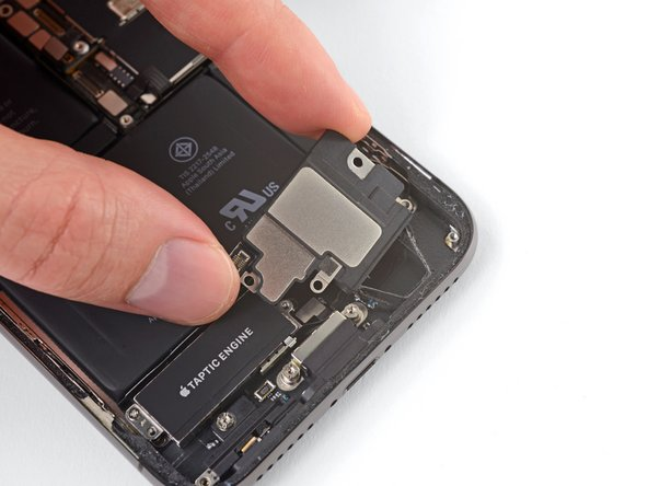 Pull the speaker away from the bottom edge of the iPhone until the adhesive gasket separates.