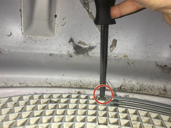 Using the Phillips #0, remove three 25.4 mm screws that hold the lint trap to the dryer.