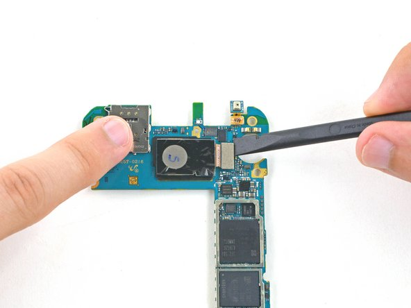Image 1/3: Remove the rear facing camera from the motherboard.