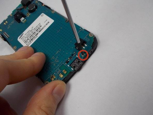 Use a philips-head screwdriver to remove the single screw on the bottom of the phone. Located to the right of the charging port.