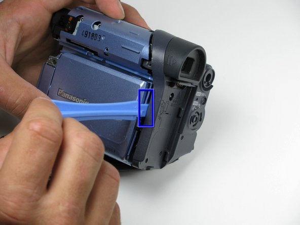 Move the plastic opening tool up the side of the camcorder as shown, carefully separating the LCD panel from the rest of the camcorder.