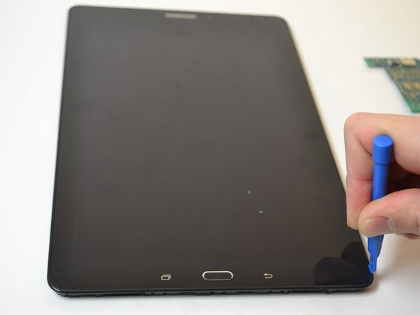 Insert a plastic opening tool between the screen and bezel.