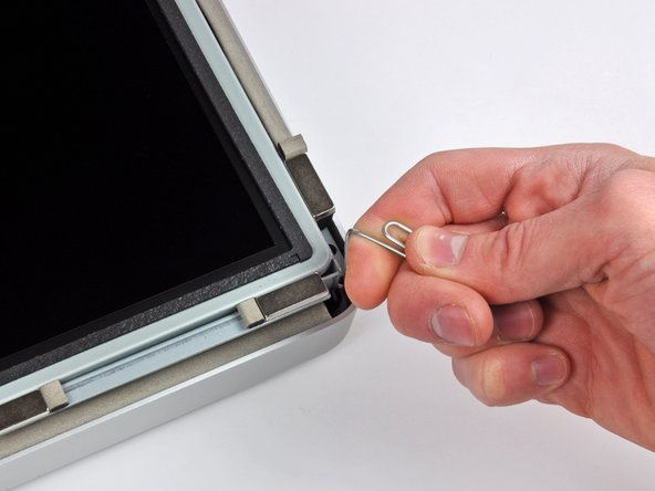 Image 2/3: Use a thin hooked tool to lift one side of the top edge of the display by its steel outer frame.