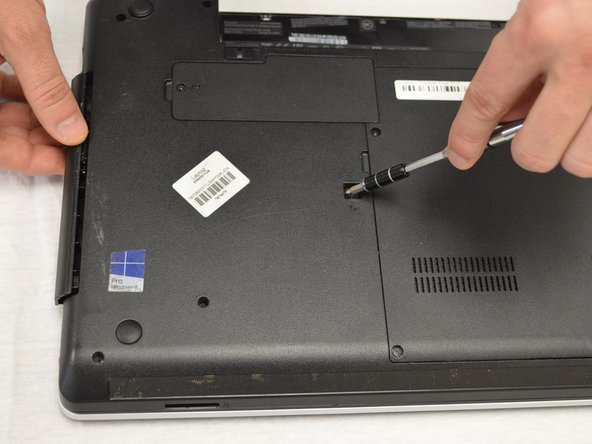 Use the end of the screwdriver to  assist in starting to  slide the optical drive out.