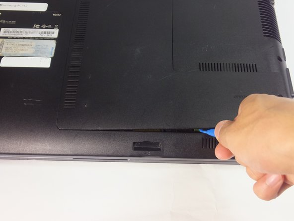 Using the blue plastic opening tools, wedge one in between the back panel and the laptop.