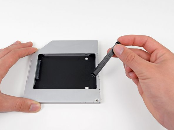 Remove the plastic positioner from the optical bay hard drive enclosure by pressing in on one of the clips on either side and lifting it up and out of the enclosure.