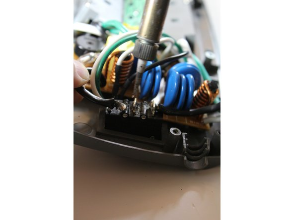 Once the solder has melted on the switch, use a pair of flat-head pliers to remove the wire.