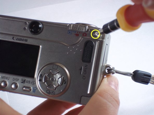 Remove one 1.6mm Phillips screw from the above the CF open button on back of the camera.