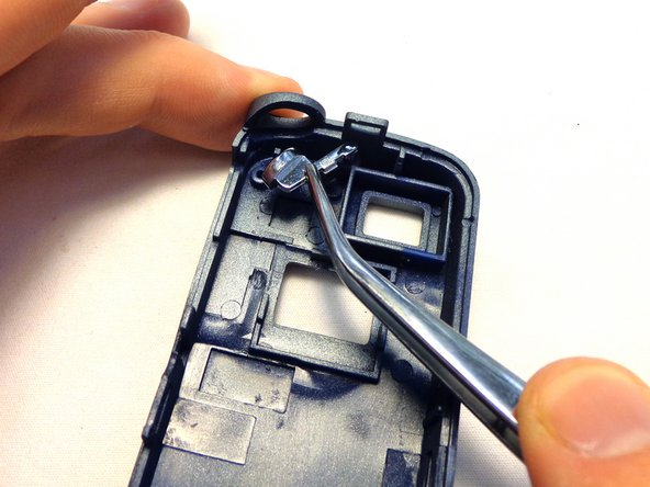 Use the tweezers to grasp the bottom of the capture button.  Pull the capture button away from the case and set it aside.