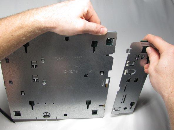 Inserte el extremo plano de un spudger en la ranura de la placa de montaje de la placa base y presione la pestaña de liberación mientras empuja la placa de extensión hacia la derecha con los pulgares hasta que se desprenda.