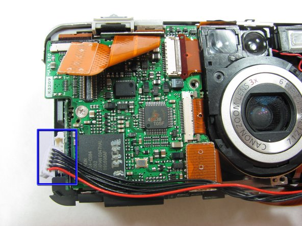 Disconnect the black and red cable on the left side of the lens.