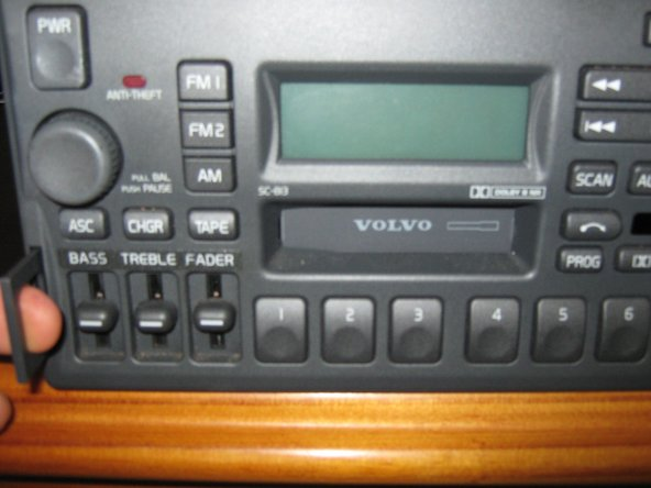 Insert your fingers into the holes on both tabs, and gently slide the radio out.  You will NOT need to disconnect the power, and antenna connections.