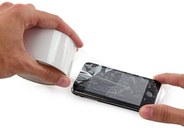 Image 2/3: Lay overlapping strips of clear packing tape over the iPhone's display until the whole face is covered.