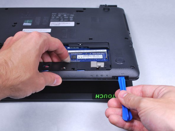 Use the plastic opening tool to gently pry open the laptop.