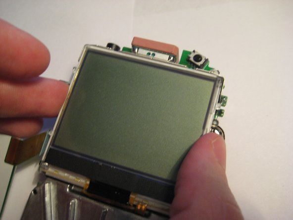 Pivot the LCD screen, pulling on the top and sides and keeping the bottom attached.