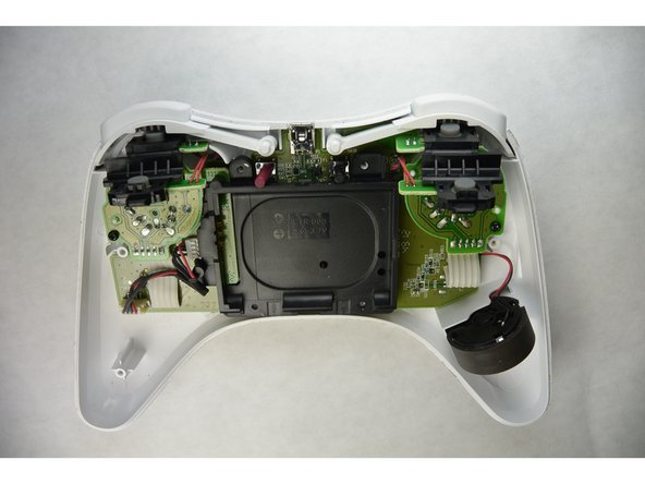 Now that you have removed all of the screws, separate and remove the bottom half of the controllers shell from the top half .