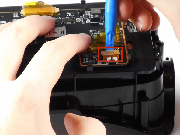 Lift the tape and gently pry up the video data ribbon cable using the plastic opening tool as shown.