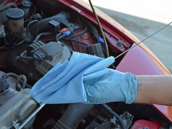 Remove the dipstick and wipe it off with a clean rag or towel.