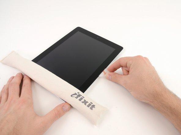 """Wenn das Opening Pick im Kleber hängen bleibt, """"walze"""" das Pick entlang der Seitenkante des iPads und löse dabei weiter den Kleber."""