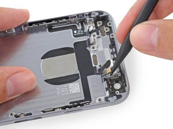 Image 3/3: If you encounter significant adhesive, use tweezers to peel the components up from the rear case.
